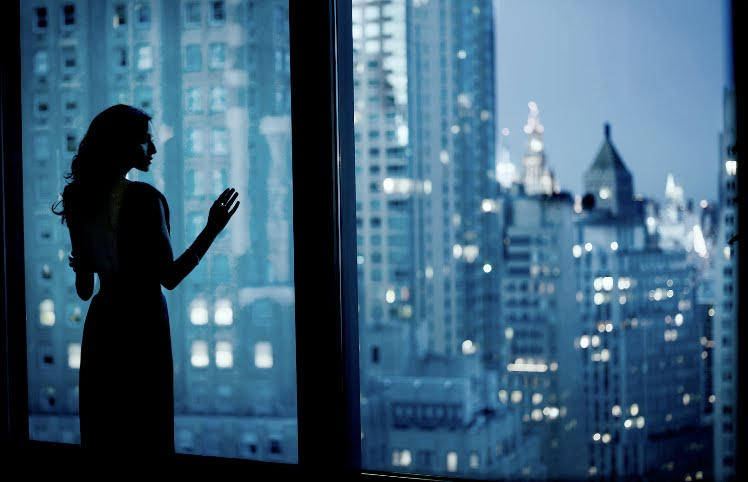 woman_looking_out_windows-urban_city_view_skyscrapers_evening_night_blue_black_white_troy_house_photography